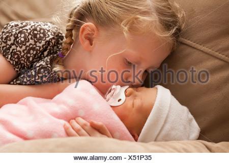 Stati Uniti d'America,Utah,Lehi,ragazza (2-3) abbracciando la sorella del bambino sul divano Foto Stock