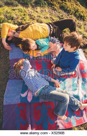 Padre e tre bambini giacente sulla coperta picnic Foto Stock