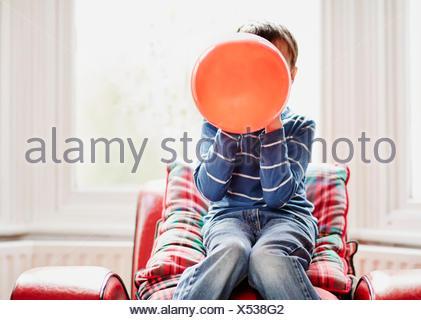 Giovane ragazzo palloncino di contenimento nella parte anteriore del viso Foto Stock