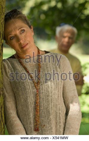 Una donna appoggiata su un albero, uomo sfocato in background. Foto Stock