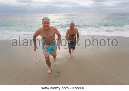 ee502926bf79 Ritratto di due uomini a nuotare in mare · Senior uomo e amico in costume  da bagno in esecuzione dal mare, sorridente, ritratto