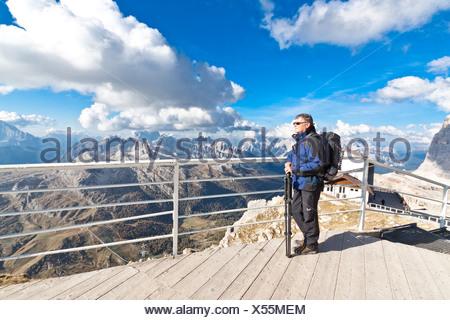 Turismo a maschio, 55, godendo la vista dal terrazzo del Rifugio Lagazuoi mountain inn, 2752 m, Passo Falzarego, Dolomiti, Italia