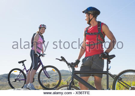 Montare il ciclista giovane in piedi al vertice sorridente ad ogni altro Foto Stock