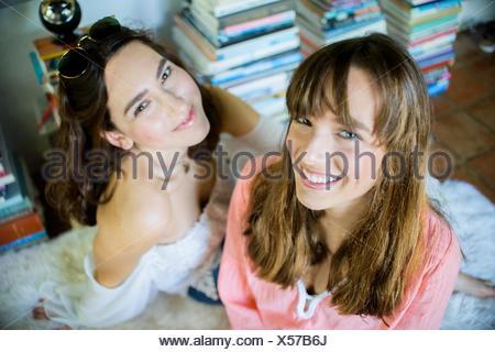 Ritratto di due giovani amici di sesso femminile seduta sul pavimento Foto Stock