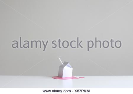 Concettuale di cartone di latte con paglia su un pool di fragola rosa millk Foto Stock