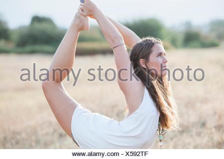 Boho donna in re ballerina yoga posa in campo rurale Foto Stock