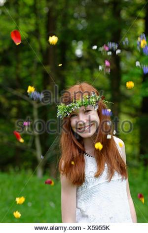 Fiore bambino, ragazza con ghirlanda di fiori nei capelli, fiori piovono