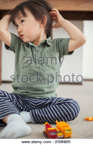 Ragazzo seduto sul pavimento con le mani nei capelli Foto Stock