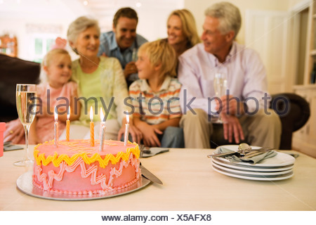 Tre generazioni la famiglia seduti sul divano di casa torta di compleanno sul tavolino in primo piano Foto Stock