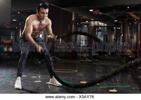 Giovani uomini esercizi in palestra Foto Stock