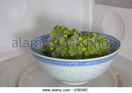 I piselli congelati lo scongelamento nel forno a microonde Foto Stock