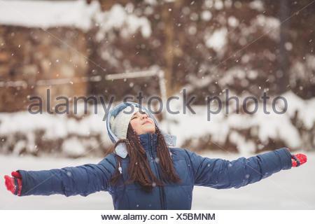 Ragazza in piedi nella neve guardando il cielo con le braccia tese Foto Stock