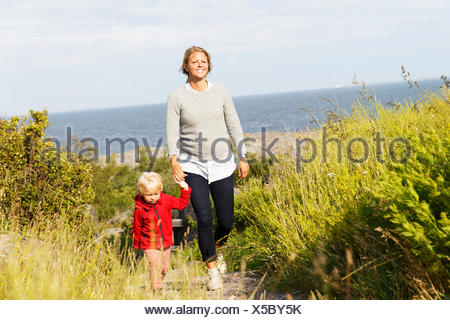 La Svezia, arcipelago di Stoccolma, Sodermanland, Oja, Donna camminare con il figlio (2-3) lungo il percorso attraverso l'erba verde Foto Stock