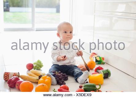 Baby rendendo il disordine sul pavimento con i prodotti alimentari Foto Stock