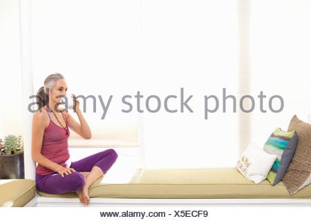 Donna seduta sul sedile della finestra di bere il tè alle erbe Foto Stock