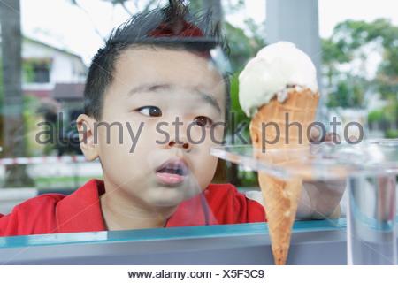 Ragazzo che guarda al cono gelato attraverso il vetro Foto Stock