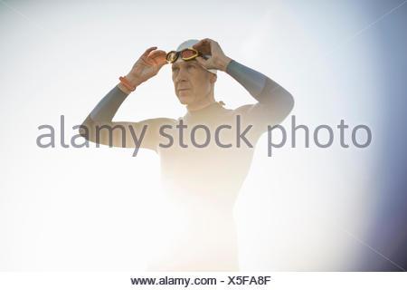 Un nuotatore in una muta e nuoto hat, regolando i suoi occhiali da nuoto. Foto Stock
