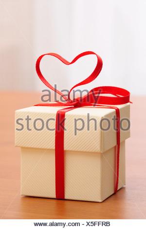 Un regalo con un cuore nastro sagomato su di esso