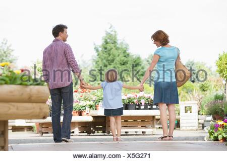 I genitori tenendo la mano figlia in vivaio Foto Stock