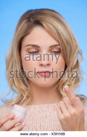 Close-up di una donna azienda crema idratante Foto Stock