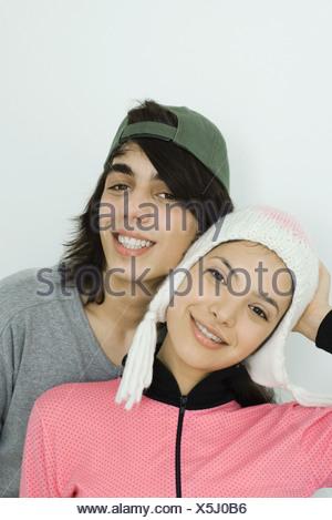 Coppia giovane sorridente in telecamera insieme, sia indossando cappelli, guancia a guancia, ritratto Foto Stock