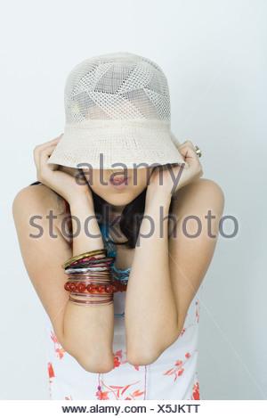 Ragazza adolescente tirando hat verso il basso oltre la faccia, rendendo volti, ritratto Foto Stock