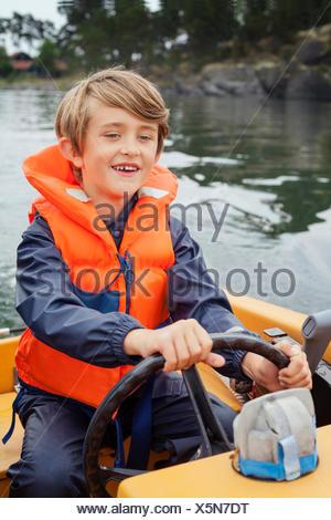 La Svezia, Uppland, Runmaro, Barrskar, ragazzo (6-7) motoscafo dello sterzo Foto Stock
