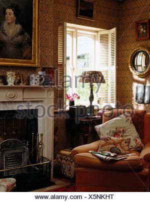 Comoda poltrona accanto al caminetto in stile vittoriano soggiorno ...