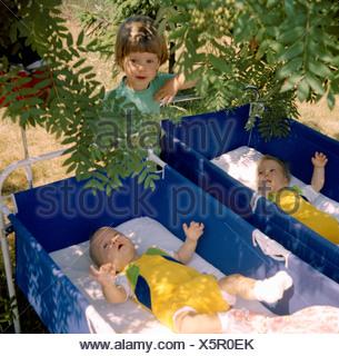 Bambino in piedi accanto a due culle Foto Stock