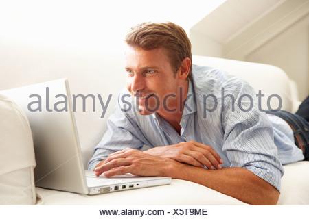 Uomo con notebook rilassarsi seduti sul divano di casa Foto Stock