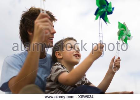 Padre e figlio giovane azienda pinwheels Foto Stock