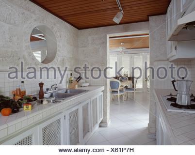 Cucina pareti bianche piastrelle ceramiche lungo tavolo sedie vino