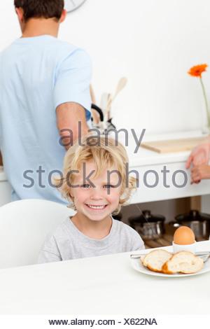 Felice ragazzo di mangiare uova sode e pane in cucina Foto Stock