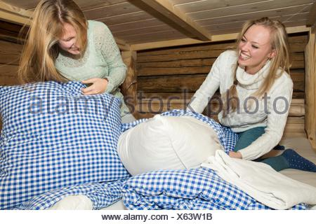 Due giovani donne amici avente cuscini lotta in log cabin Foto Stock