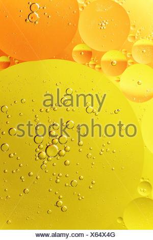 Giallo e arancione di goccioline di olio in acqua Foto Stock