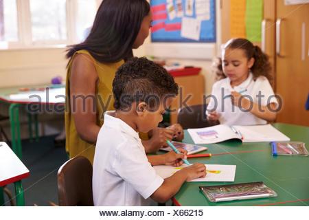 Femmina di insegnante di scuola elementare aiutare gli alunni a scrivania Foto Stock