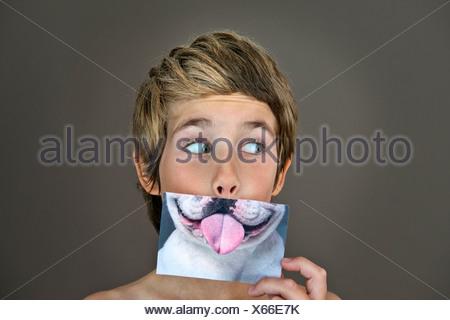 Ragazzo holding immagine del cane oltre la faccia Foto Stock