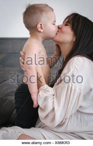 Un fortemente incinta Donna baciare il suo giovane figlio. Foto Stock