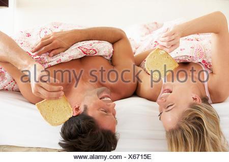 Giovane rannicchiò sotto piumone di mangiare la prima colazione Foto Stock