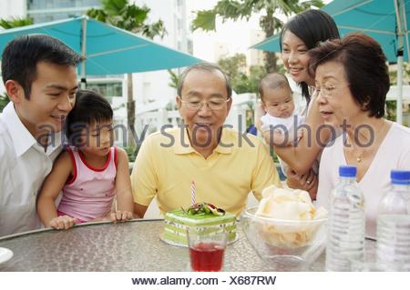 Tre generazioni della famiglia nonno festeggia il compleanno Foto Stock
