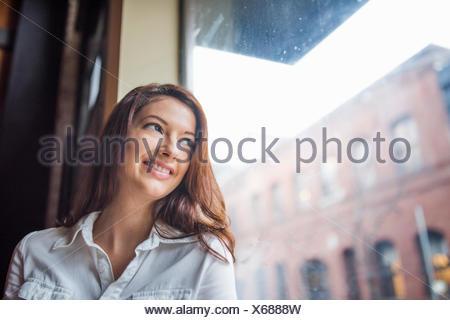 Ritratto di giovane donna con lunghi capelli scuri, sorridendo a basso angolo di visione