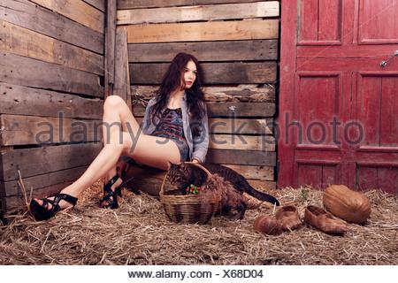 La ragazza con un gatto in hay tinti in colori luminosi. Foto Stock
