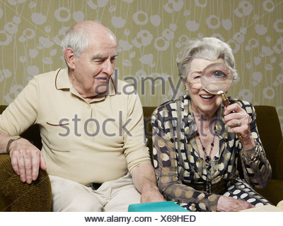 Senior uomo divertito come senior donna ingrandisce l'aspetto del suo occhio con lente di ingrandimento Foto Stock