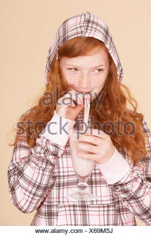 Ragazza giovane interni bere frullato fragole Foto Stock