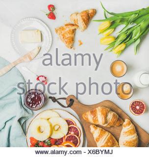 Tavolo per la colazione con cornetti, burro, marmellata di lamponi, frutta fresca, latte in bottiglia, caffè espresso e molla tulipano giallo fiori. Vista superiore, copia s Foto Stock