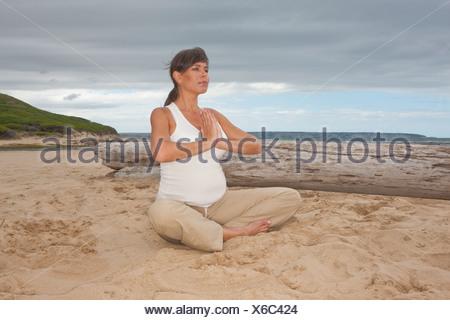 Gravidanza metà donna adulta a praticare yoga sulla spiaggia Foto Stock