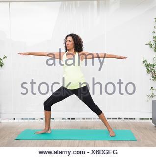 Donna matura facendo yoga posa guerriero