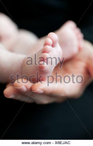 Del bambino in piedi. Madre mentre tiene il suo bimbo di due mesi i piedi. Foto Stock
