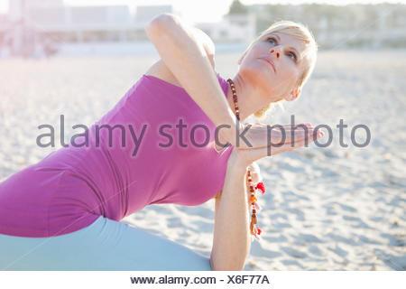 Donna in preghiera yoga pone sulla spiaggia Foto Stock