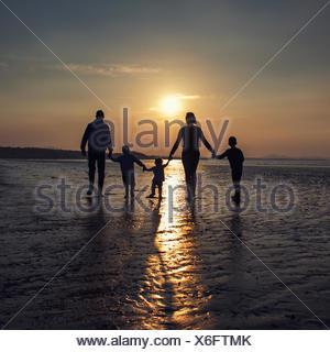 Silhouette di una famiglia sulla spiaggia tenendo le mani Foto Stock